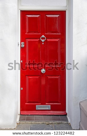 Red entrance door in front of residential house #123224482