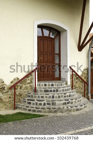Red entrance door with round staircase