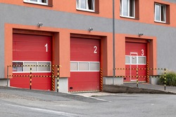 Red entrance gates to a Czech fire station where the fire trucks are parked and ready for emergency situation