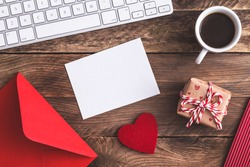 Red envelope on a wooden table in the office. Love letter, Valentines card, holiday letter gift and cup of coffee on office desk.