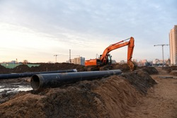 Red excavator during groundwork on construction site. Hydraulic backhoe on earthworks. Heavy equipment for demolition, construction and ground works. Digging foundation and laying storm sewer pipes