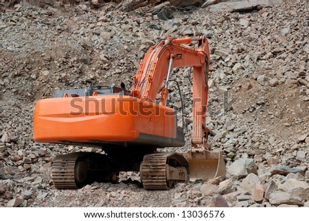 Red excavator in a stone pit