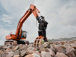 Red excavator with rock or stone grab attached to the arm. Heavy machinery equipment on a construction site