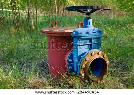 Red expansion pipe of drink water pipes joined with new blue valve and new blue joint members. New dump valve. Metal corroded texture.