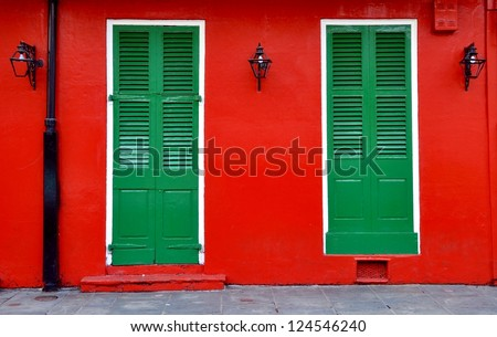 Red Exterior Wall With Green Shuttered Doors And Lanterns In New Orleans French Quarter