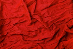 Red fabric background. Texture and folds of red fabric, copy space.