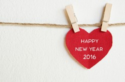 Red fabric heart with happy new year 2016 word hanging on the clothesline, new year template