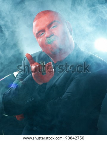 Red faced dangerous man smoking cigar on scary background close up.