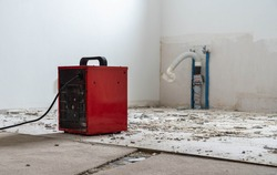 red fan heater at a construction site, remnants of tile adhesive and drain pipes in the background