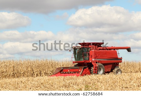 Red farm combine harvesting corn against a blue sky with clouds