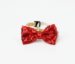 red fashionable bow tie with sequins for the neck on an elastic band, accessory on a white background