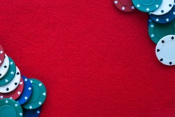 Red felt table with poker chips over it and copy space. Casino, gambling, poker and roulette theme background