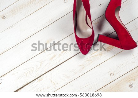 Red female shoes on high heels isolated on white wooden background #563018698
