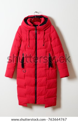 Red female winter jacket with a hood without fur, with a zipper. Outerwear. A long crimson jacket, isolated on a gray background. - Shutterstock ID 763664767