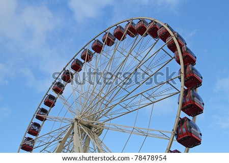 Red Ferris Wheel with blue sky as the background