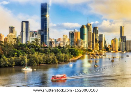 Red ferry transporting passangers during morning communte across Brisbane river in Brisbane city in front of city CBD waterfront seen from elevation of cliffs park.