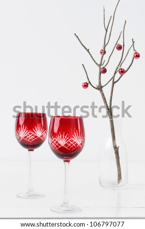 Red festive christmas wine glasses on table with minimalist christmas tree