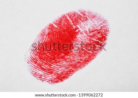 Red fingerprint on white background. Friction ridge pattern #1399062272