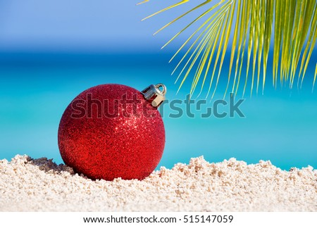Red fir tree decoration ball on sandy beach with palm tree leaves, Tropical christmas and New Year celebration  #515147059