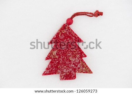 red fir tree toy on snow background