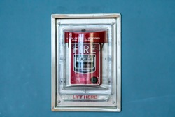 red fire alarm behind a glass cover or door against a blue wall surface in a building