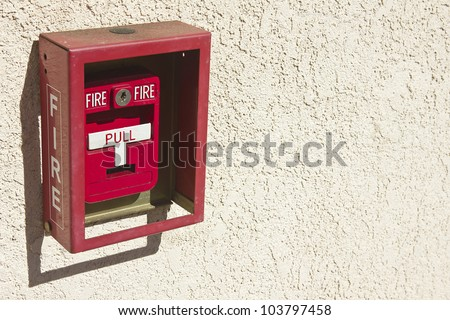 Red fire alarm box with white pull handle.