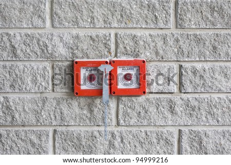red fire alarm on gray brick wall