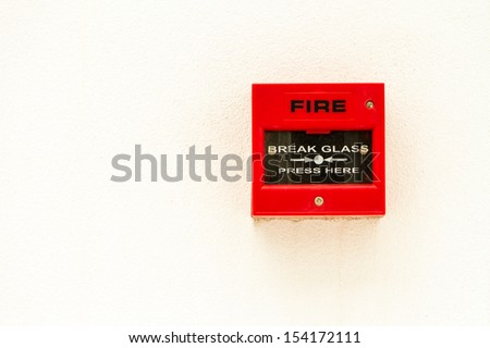 Red fire alarm switch on white concrete wall.