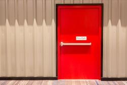 Red fire exit door in an office building.
