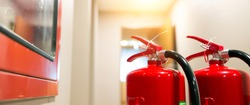 Red fire extinguisher tank at the exit door in the building concepts of emergency safety for fire prevention rescue and fire services concetps.