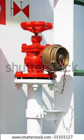 Red fire hydrant on a white pipe with a copper cover