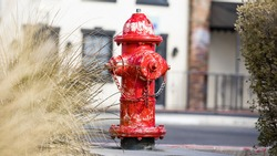 Red fire hydrant with chipped and peeling paint. Surrounding grass and European style building in bokeh. Captured with a shallow depth of field with focus on the hydrant.