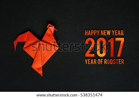 Red fire paper folded rooster handmade origami craft on black background. Nice horizontal holiday greeting card, postcard. Happy new year 2017 year of rooster text letters.