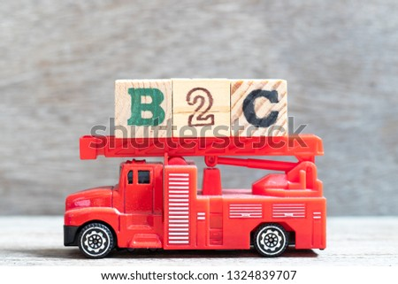 Red fire truck hold letter block in word b2c (Abbreviation of business to consumer) on wood background