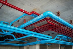 Red fire water pipes on the concrete wall in the condo building.Installation of drainage pipes in the building.Sanitary system of a condominium.water piping system install with the concrete ceiling.