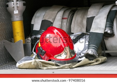 Red firefighter helmet and hose