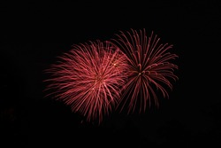 Red firework bursts in the night sky