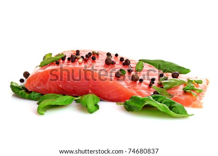 Red fish with pepper and green leaves isolated on white