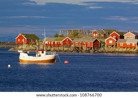 Red fishing rorbu huts and fishing boat in town of Reine on Lofoten islands