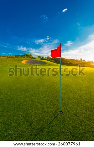 Red flag and sand bunker at the beautiful golf course at sunset, sunrise time. Vertical.