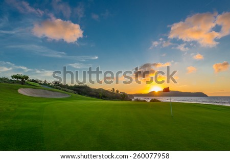 Red flag and sand bunker at the beautiful golf course at the ocean side at sunset, sunrise time.