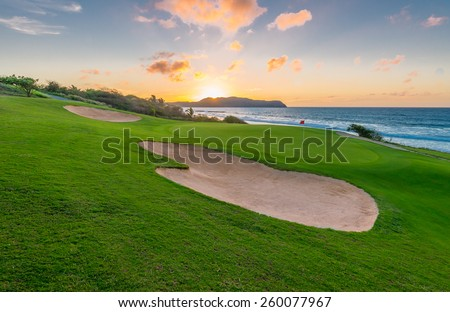 Red flag and sand bunkers at the beautiful golf course at the ocean side at sunset, sunrise time.