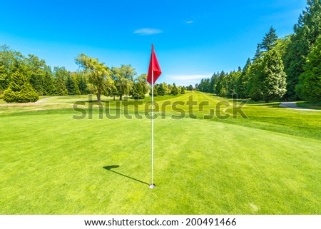 Red flag at the beautiful golf course in a sunny day. Canada, Vancouver.