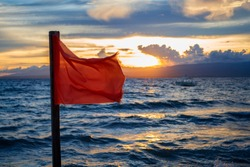 Red flag by the sea with sunset background. Evening seaside scene with danger warning sign. Beach warning flag splashing on wind. Stormy sea threat warning. Vacation danger. Extreme seawater caution