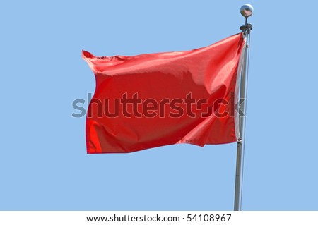 Red flag flying in a stiff breeze against a clear blue sky.