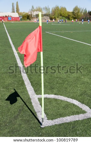 Red flag in corner of soccer field in summer day