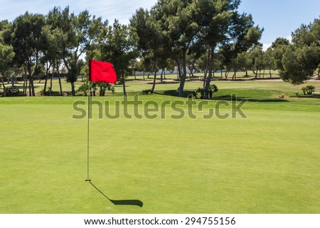 Red flag in the hole on a green golf field golf course