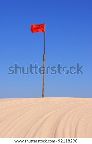 Red flag marker on the racing track in sand