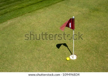 Red flag marks the golf hole on putting range