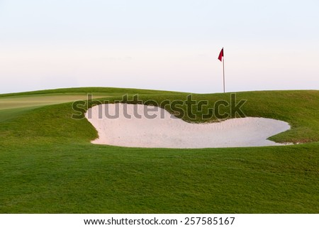 Red flag of golf hole above sand trap or bunker on beautiful course at sunset